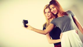 Two models girls taking self picture with camera Stock Photo