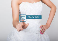 Technology, internet and networking concept. Beautiful bride in fashion wedding dress. Bride presses check mail button Royalty Free Stock Images