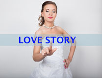Technology, internet and networking concept. Beautiful bride in fashion wedding dress. Bride presses love story button Royalty Free Stock Image