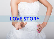 Technology, internet and networking concept. Beautiful bride in fashion wedding dress. Bride presses love story button Stock Photos