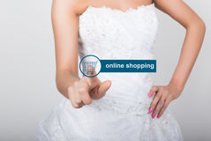 Technology, internet and networking concept. Beautiful bride in fashion wedding dress. Bride presses online shopping. Button on virtual screens Royalty Free Stock Photos