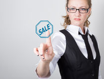 Technology, internet and networking concept. beautiful woman in a black business shirt. woman presses sale button on Stock Photos