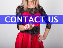 Technology, internet and networking concept. beautiful woman in a red dress with lace sleeves. woman presses contact us Royalty Free Stock Images