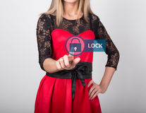 Technology, internet and networking concept. beautiful woman in a red dress with lace sleeves. woman presses lock button Royalty Free Stock Images