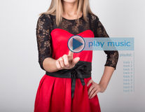 Technology, internet and networking concept. beautiful woman in a red dress with lace sleeves. woman presses play music Royalty Free Stock Photos