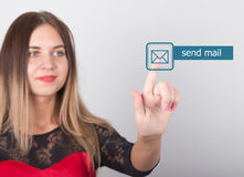 Technology, internet and networking concept. beautiful woman in a red dress with lace sleeves. woman presses send mail Royalty Free Stock Photo