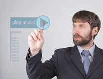 Technology, internet and networking concept - Businessman presses play music button on virtual screens. Internet Royalty Free Stock Images