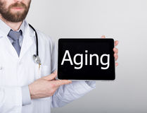 Technology, internet and networking in medicine concept - Doctor holding a tablet pc with aging sign. Internet. Technologies in medicine Royalty Free Stock Photos