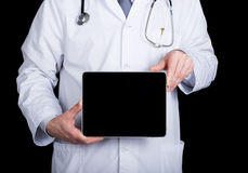 Technology, internet and networking in medicine concept - Doctor holding a tablet pc with a blank dark screen. Internet Stock Image