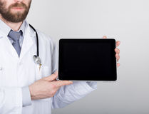 Technology, internet and networking in medicine concept - Doctor holding a tablet pc with a blank dark screen. Internet Stock Photography