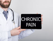 Technology, internet and networking in medicine concept - Doctor holding a tablet pc with chronic pain sign. Internet Royalty Free Stock Image