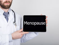 Technology, internet and networking in medicine concept - Doctor holding a tablet pc with menopause sign. Internet Stock Photos