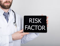Technology, internet and networking in medicine concept - Doctor holding a tablet pc with risk factor sign. Internet Stock Images