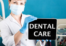 Technology, internet and networking in medicine concept - femail dentist holding a tablet pc with dental care sign. at Royalty Free Stock Photography