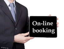 Technology, internet and networking in tourism concept - businessman holding a tablet pc with on-line booking sign. Internet technologies in business and Royalty Free Stock Images