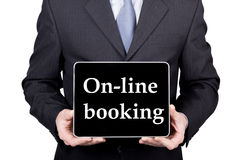 Technology, internet and networking in tourism concept - businessman holding a tablet pc with on-line booking sign. Internet technologies in business and Royalty Free Stock Photography