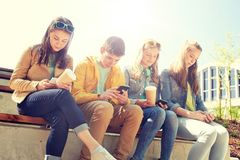 Teenage friends with smartphone and coffee cups. Technology, internet and people concept - group of happy teenage friends with smartphone and coffee cups Royalty Free Stock Photo