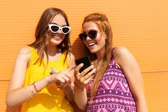Teenage girls with smartphones in summer outdoors Stock Photos