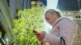 Technology in life. Young woman with a smartphone in the big city. The sun plays in her hair. Young business woman uses a smartphone in a big city. Against the stock video footage
