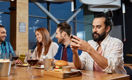 Man messaging on smartphone at restaurant stock images