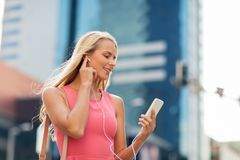 Happy young woman with smartphone and earphones Stock Photos