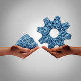 Technology Management. Concept as a hand holding a group of mixed disorganized gears and cogs with another person presenting the machine parts put together as a Royalty Free Stock Photo