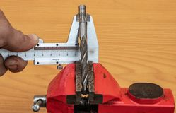 The technology of measuring the diameter of the drill, using calipers stock images