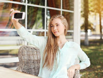 Technology, mobile and people concept - pretty girl makes self-portrait on the smartphone Stock Images