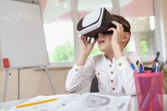 Young boy using 3d virtual reality headset at school. Technology, modern childhood concept. Little boy looking overwhelmed and excited, wearing 3d virtual royalty free stock images