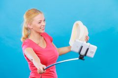 Woman taking picture of herself with phone on stick royalty free stock image