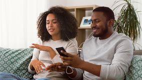 Happy couple with smartphone and earphones at home stock footage