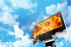 Technology and Nature. Theme. Modern Computer Display Between the Clouds. Cloudy Blue Sky. Orange Flowers on the Screen Royalty Free Stock Image