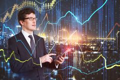 Technology, network and stock concept. Attractive young european businessman using device with glowing forex chart on blurry night city background. Technology royalty free stock images