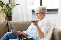 Old woman with laptop records voice by smartphone. Technology, old age and people concept - happy senior woman in glasses with laptop computer and smartphone stock photo