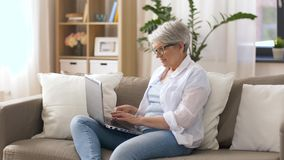 Happy senior woman typing on laptop at home. Technology, old age and people concept - happy senior woman in glasses typing on laptop at home stock video footage