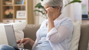 Happy senior woman typing on laptop at home. Technology, old age and people concept - happy senior woman in glasses typing on laptop at home stock footage