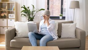 Happy senior woman typing on laptop at home. Technology, old age and people concept - happy senior woman in glasses typing on laptop at home stock video