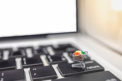 Technology, Online E-Commerce Concept. Close up of shopping cart / trolley miniature figure on computer keyboard return button stock images