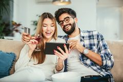 Technology, online shopping and people concept. Smiling happy couple couple with tablet pc computer and credit card at home stock image