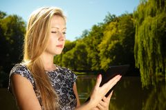 Woman sitting in park, relaxing and using tablet stock photography