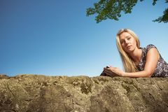 Woman sitting in park, relaxing and using phone Stock Images