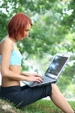 Technology outdoors. Cute young girl with laptop outdoors royalty free stock image