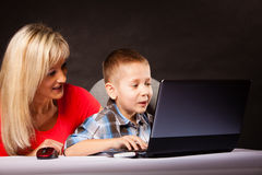 Technology and parenting - boy and mother with laptop. Education, technology, internet and parenting concept - boy and mother with laptop computer stock photography