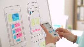 Woman working on smartphone interface design stock footage