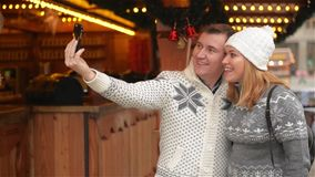 Technology and People concept. Happy Couple of Tourists in Warm Clothes Taking Selfie with Smartphone on the Christmas stock video footage