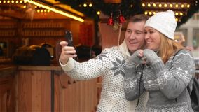 Technology and People concept. Happy Couple of Tourists in Warm Clothes Taking Selfie with Smartphone on the Christmas stock video