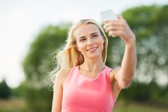 Happy woman taking selfie with smartphone outdoors Stock Photo