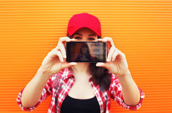 Technology and people concept - pretty girl makes self-portrait Royalty Free Stock Photo