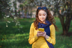 Technology and people concept - smiling young woman texting on smartphone Royalty Free Stock Images