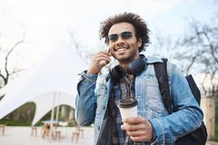 Technology and people concept. Young handsome dark-skinned male with bristle and afro haircut talking on cellphone while. Drinking coffee and walking around Royalty Free Stock Photos